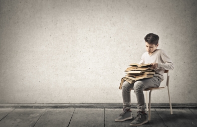 Teenage male on chair with pile of books (Shutterstock)