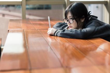asian-female-leaning-on-desk-shutterstock