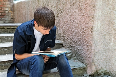 male-student-on-step-reading-shutterstock