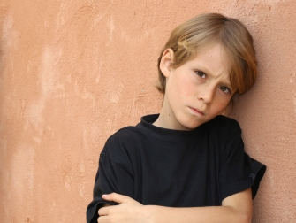 annoyed-boy-against-wall-shutterstock